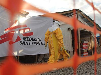 Person in protective clothing walks by a Medecins Sans Frontiers banner