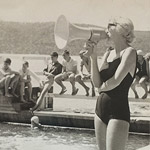 Black and white photo of a woman in a swimming costume with a megaphone