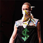 Model walking the catwalk dressed in bandana and shirt with dollar sign