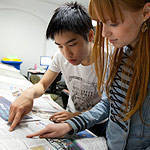 Two students looking up information in a newspaper